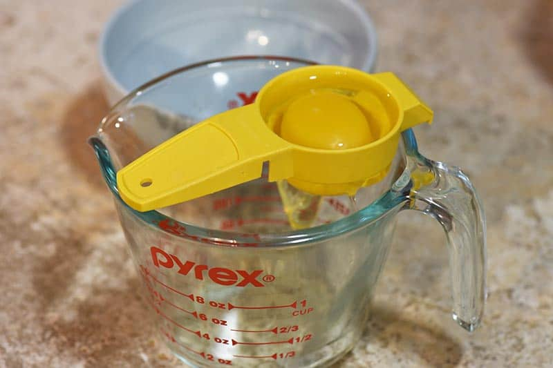 separating eggs using an egg yolk separator and a Pyrex measuring cup for chocolate cupcakes recipe