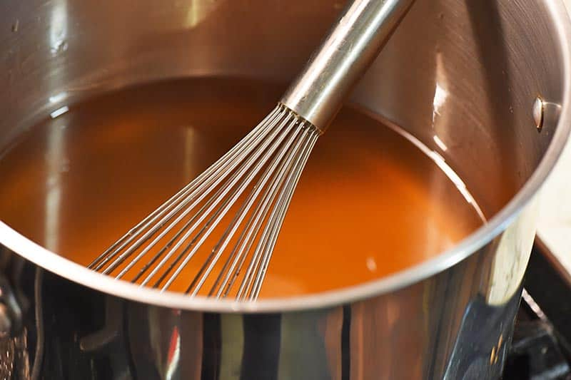 cooking apple jelly in a stock pot with a whisk