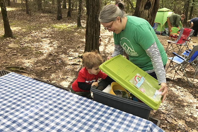 mom and toddler getting camping cooking gear on Petit Jean State Park campground picnic table in campsite