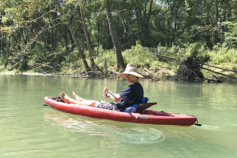 teen boy kayaking on the clear water of the Current River, one of the best float trips in Missouri