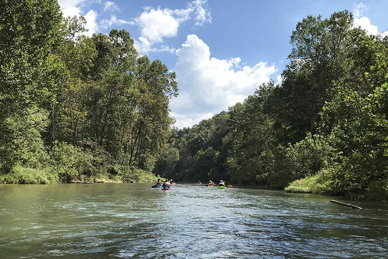 kayaking over ripples on the Current River in Ozark National Scenic Riverways