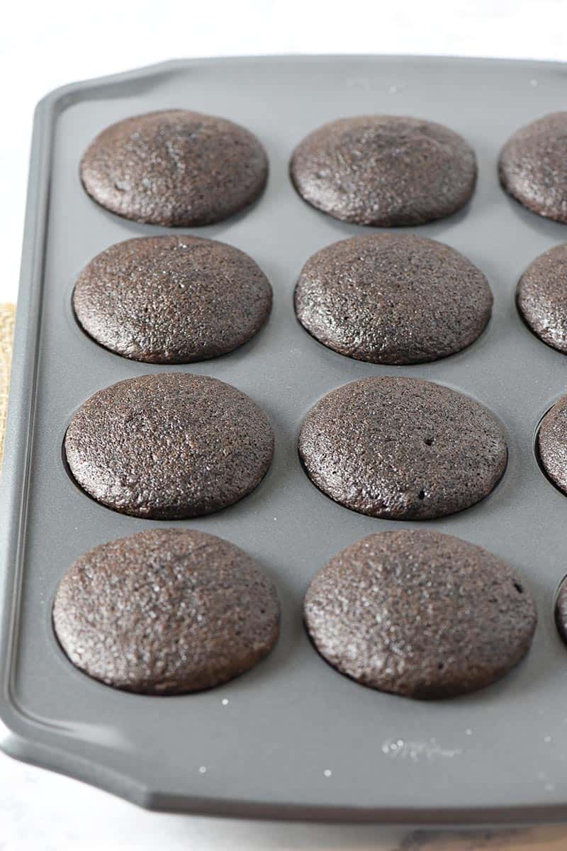 baked chocolate cupcakes in muffin pan on white marble countertop