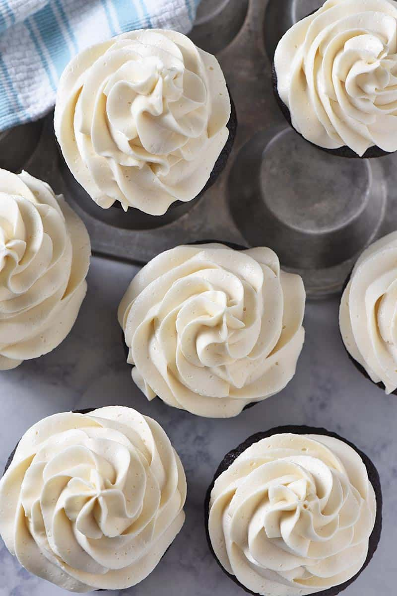 easy butterbeer buttercream frosting swirled onto chocolate cupcakes on white marble countertop with muffin tin and light blue kitchen towel