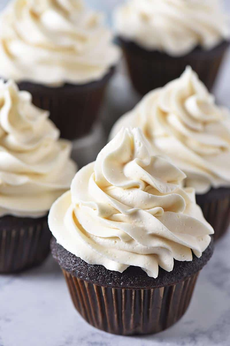easy chocolate cupcakes with butterbeer buttercream frosting and brown paper cupcake liners on a white marble countertop