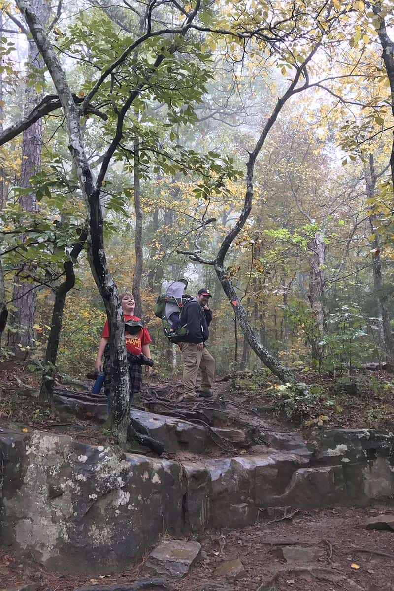 Arkansas hikers following Hawksbill Crag Trail through an autumn forest