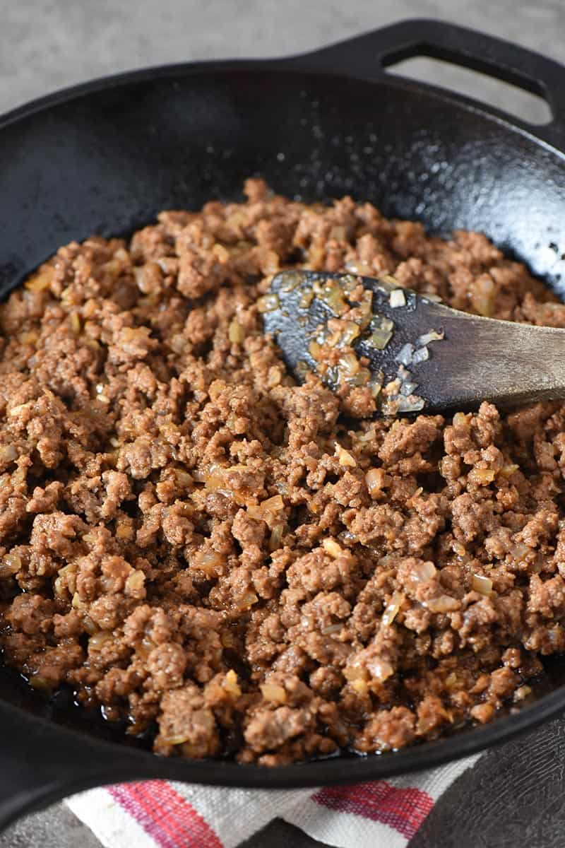 ground beef sloppy joes mixture in iron skillet with wooden spatula