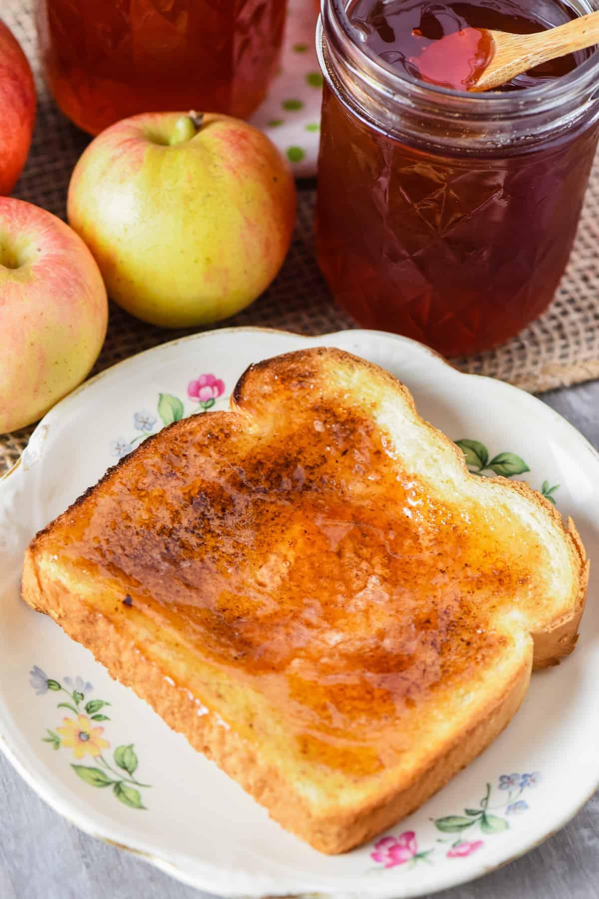 homemade apple jelly on toast on white flowered plate