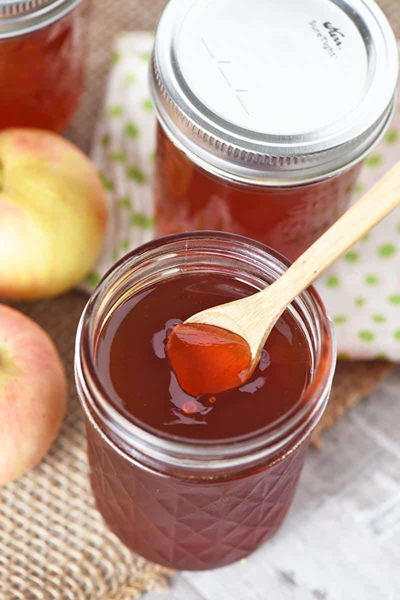homemade apple jelly with wooden spoon in it