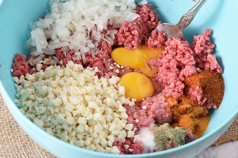 low carb meatloaf ingredients in blue mixing bowl, including ground beef, cauliflower rice, onion, eggs, and seasonings