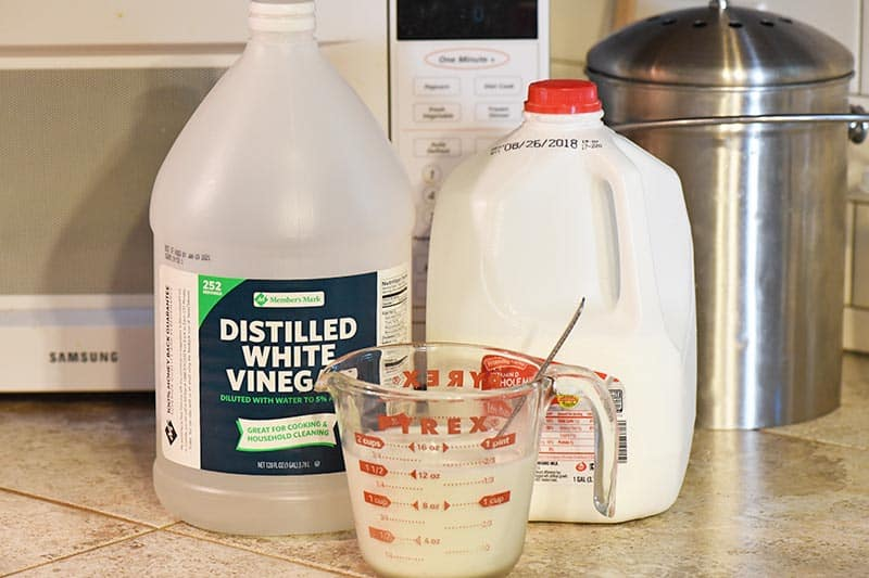 ingredients to make buttermilk for chocolate cupcakes recipe, including vinegar and whole milk, with Pyrex measuring cup on tile counterop