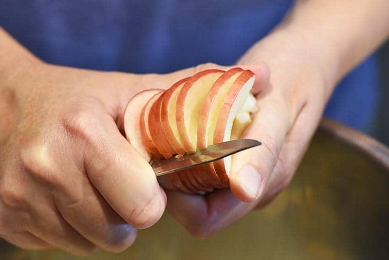 slicing apples while making cinnamon applesauce