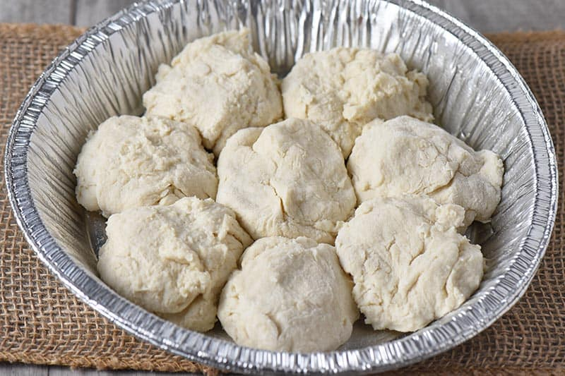 uncooked drop biscuits in a tin foil pie plate for campfire cooking