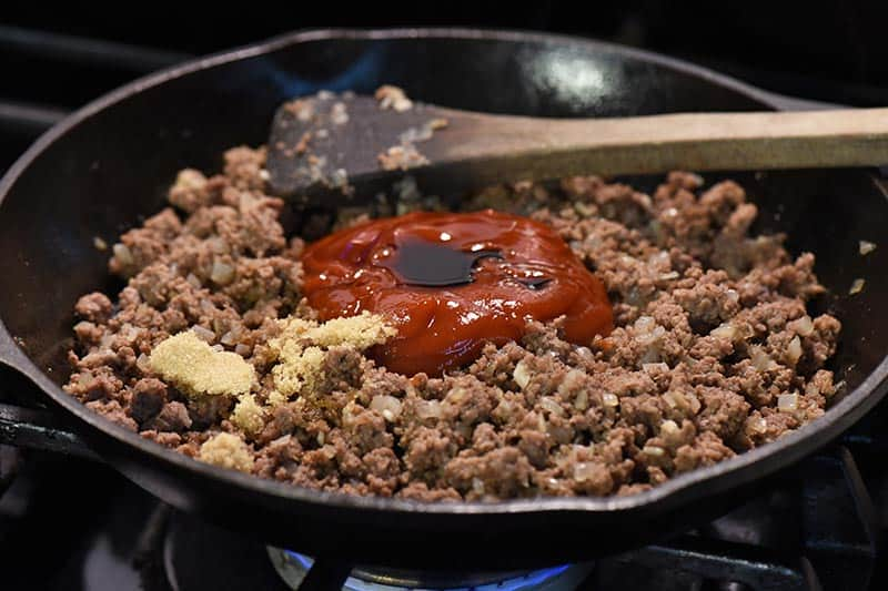 mixing ingredients for sloppy joes sauce into meat mixture in cast iron skillet on stovetop
