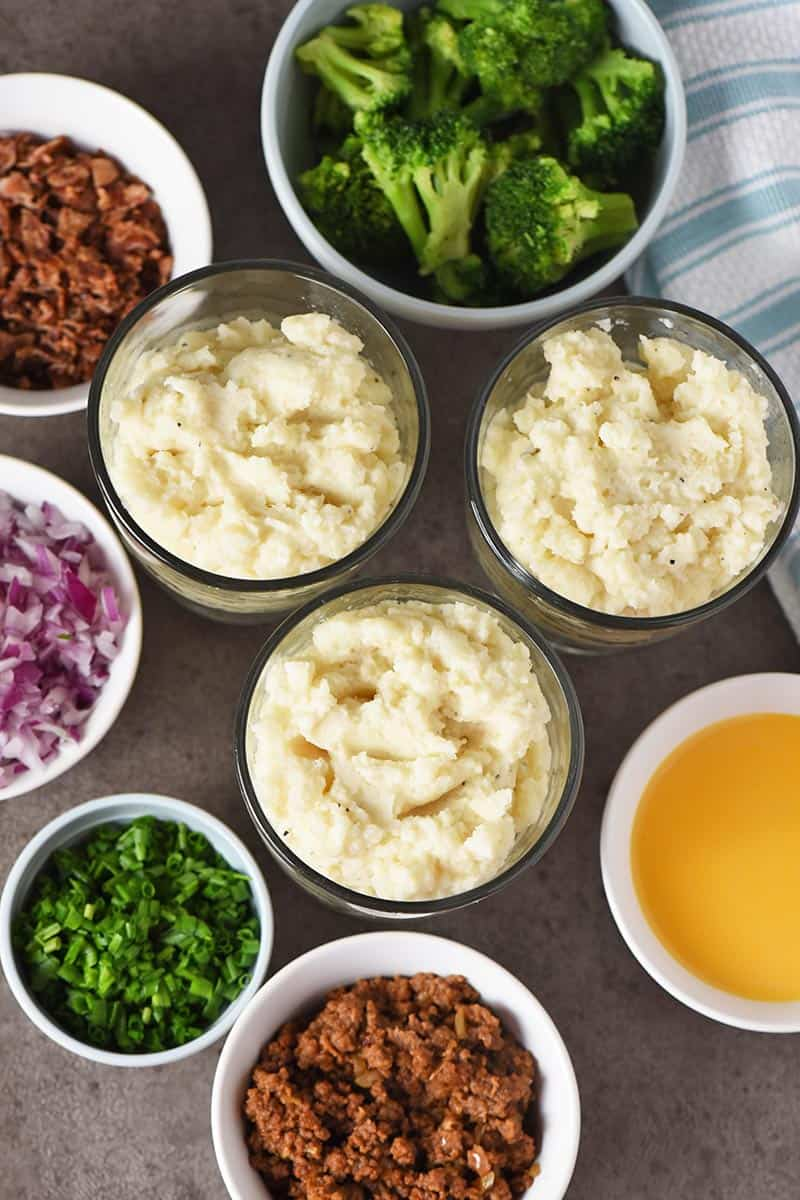 mashed potatoes with mashed potato bar toppings on gray countertop with white and blue kitchen towel