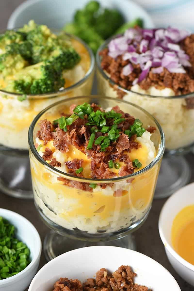 mashed potato bar with mini trifle bowls of mashed potatoes covered in toppings like bacon, cheese sauce, chives, broccoli, sloppy joe meat, and red onion
