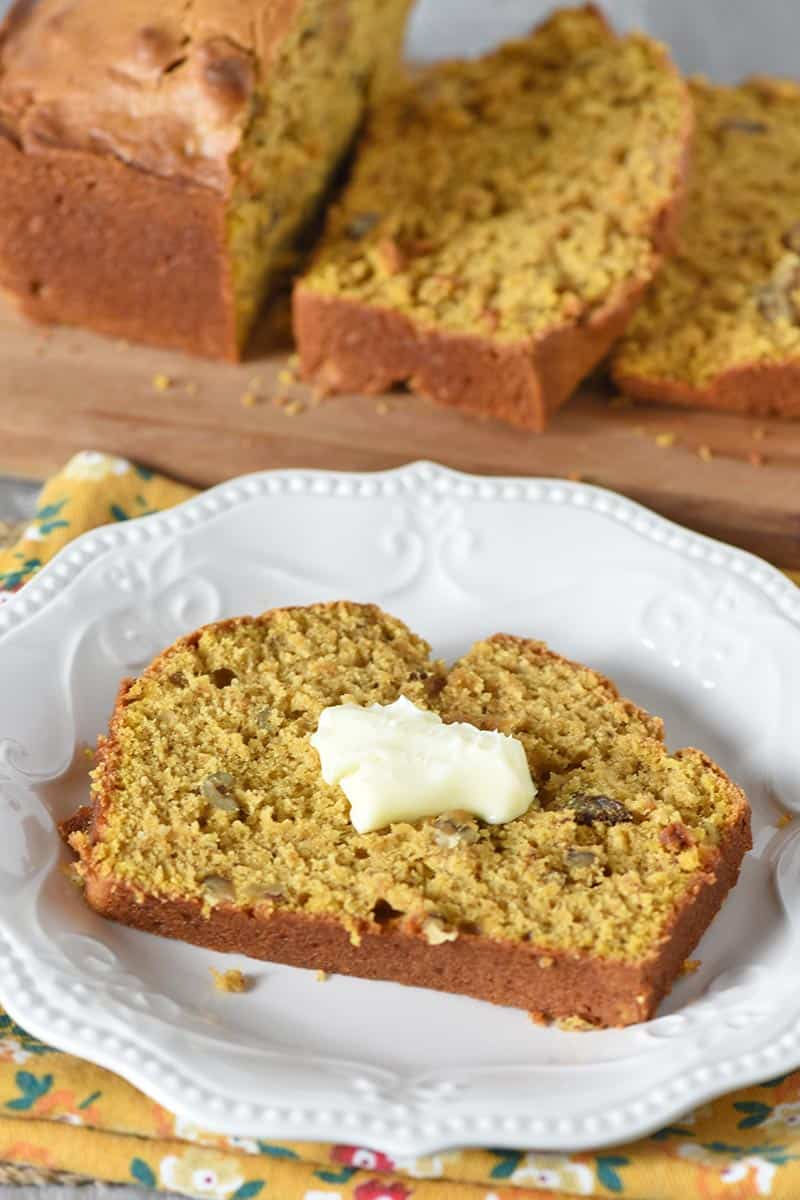 slice of pumpkin bread with butter on white plate