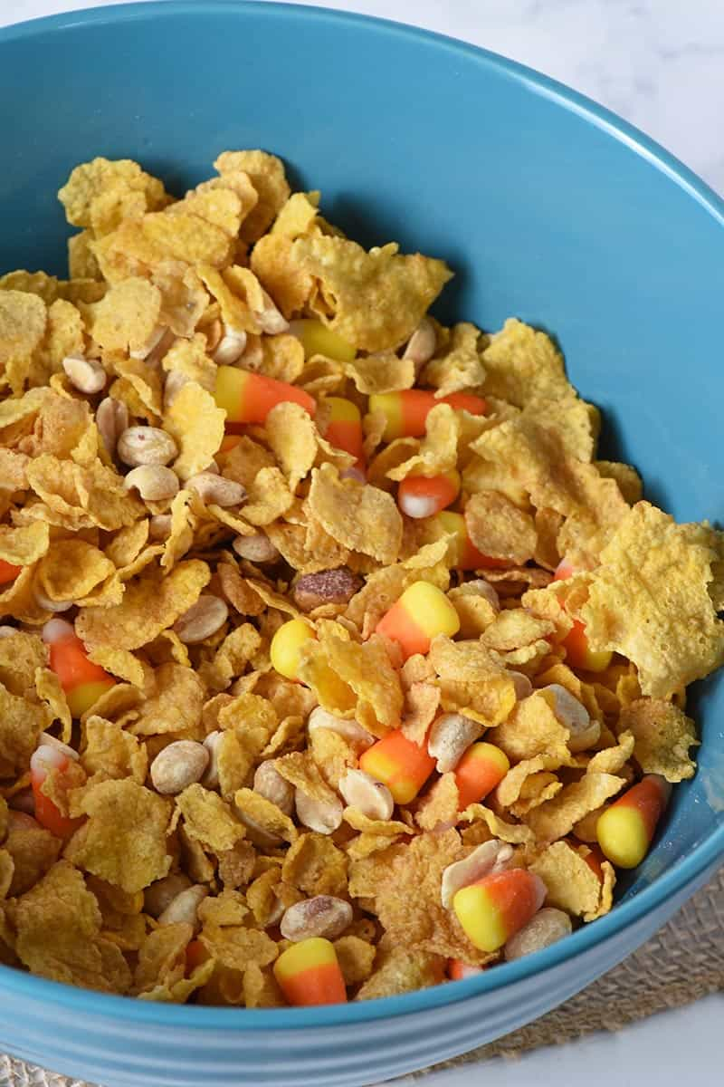 mixing together no bake peanut butter bars ingredients, including corn flake cereal, PLANTERS peanuts, and candy corn in large blue mixing bowl