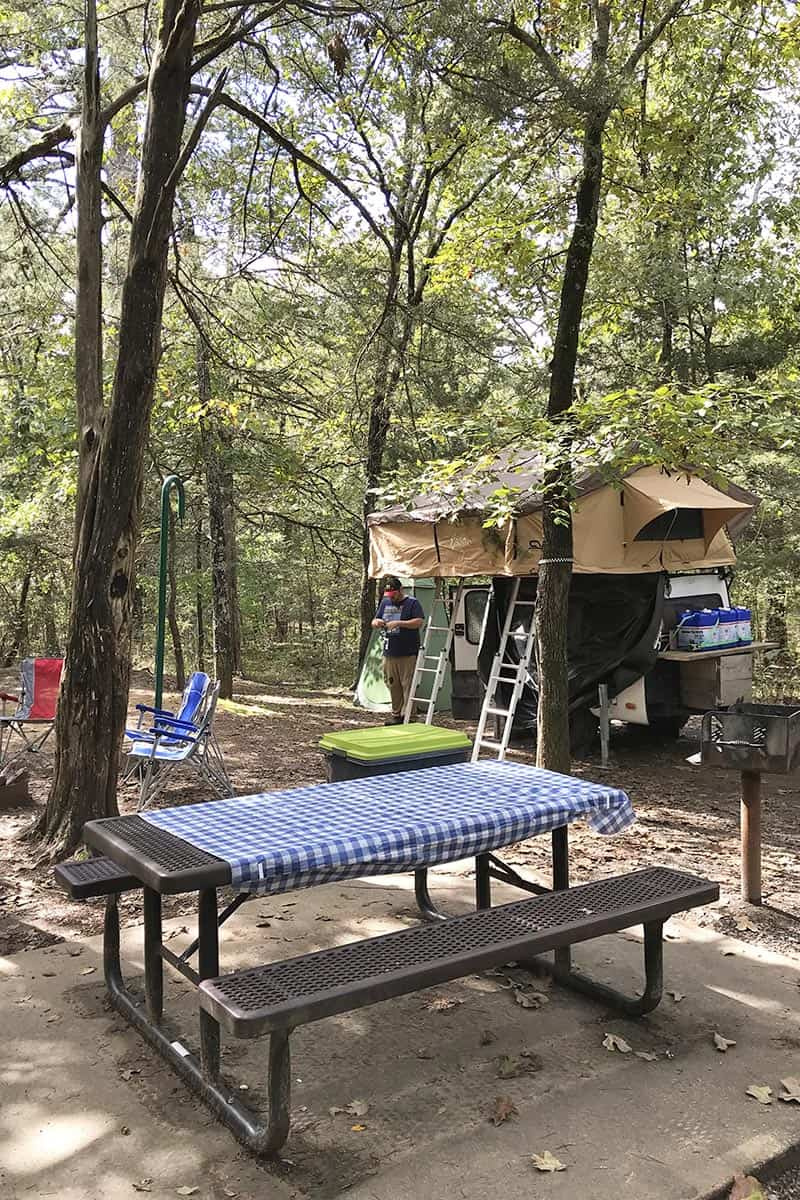 rooftop tent setup in Petit Jean State Park campground with picnic table and camping chairs
