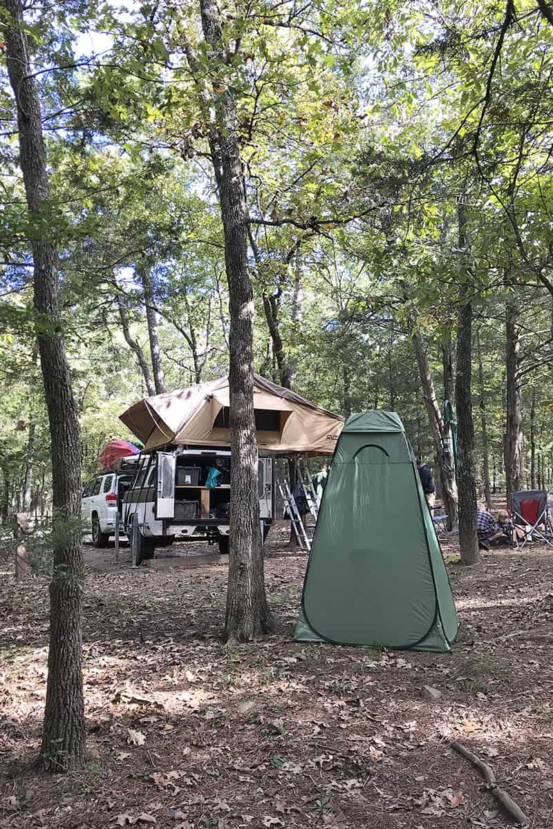 back of campsite at Petit Jean State Park with shower tent and rooftop tent with camping trailer