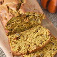 sliced loaf of homemade pumpkin bread on a wooden cutting board with a decorative pumpkin