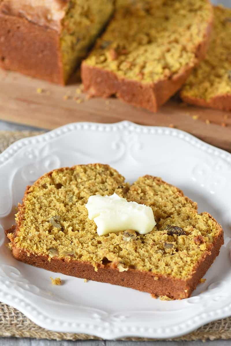 slice of moist pumpkin spice bread with butter on white plate
