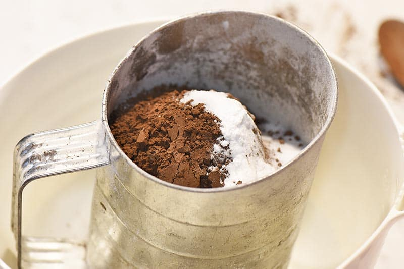 sifting dry ingredients for chocolate cupcakes into white batter bowl
