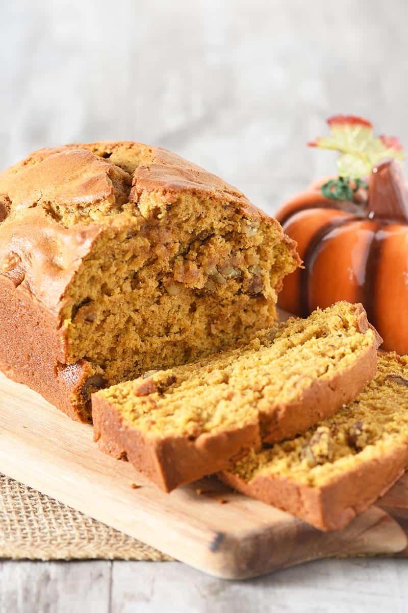 sliced pumpkin bread on cutting board with decorative pumpkin