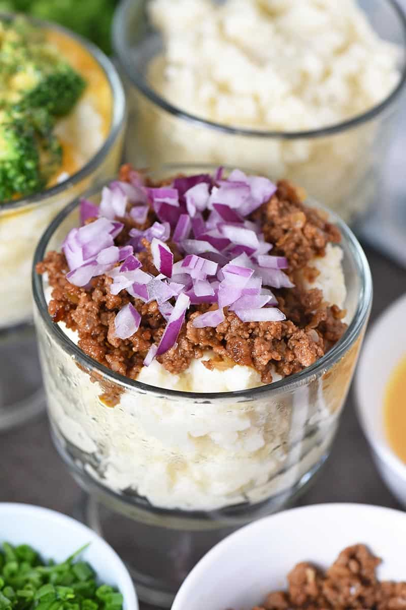 sloppy joe meat and red onions on mashed potato in small glass trifle dish