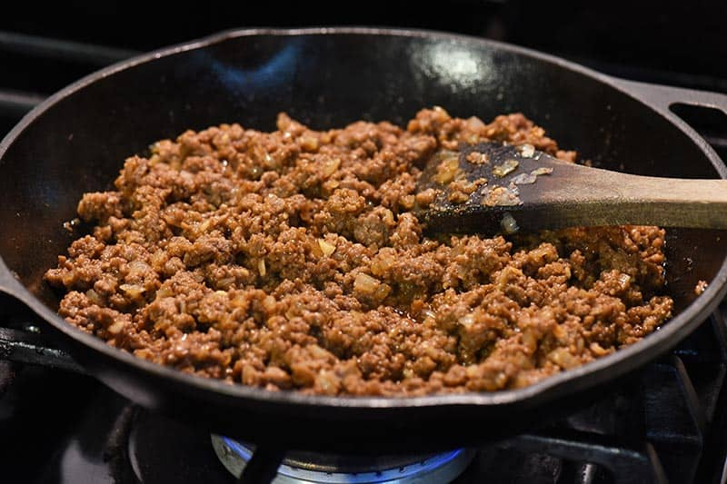 simmering sloppy joes ground beef mixture in cast iron skillet on stovetop