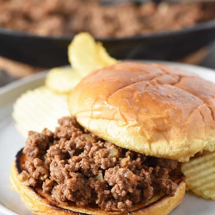 open faced sloppy joes with potato chips on gray plate and sloppy joe meat in iron skillet