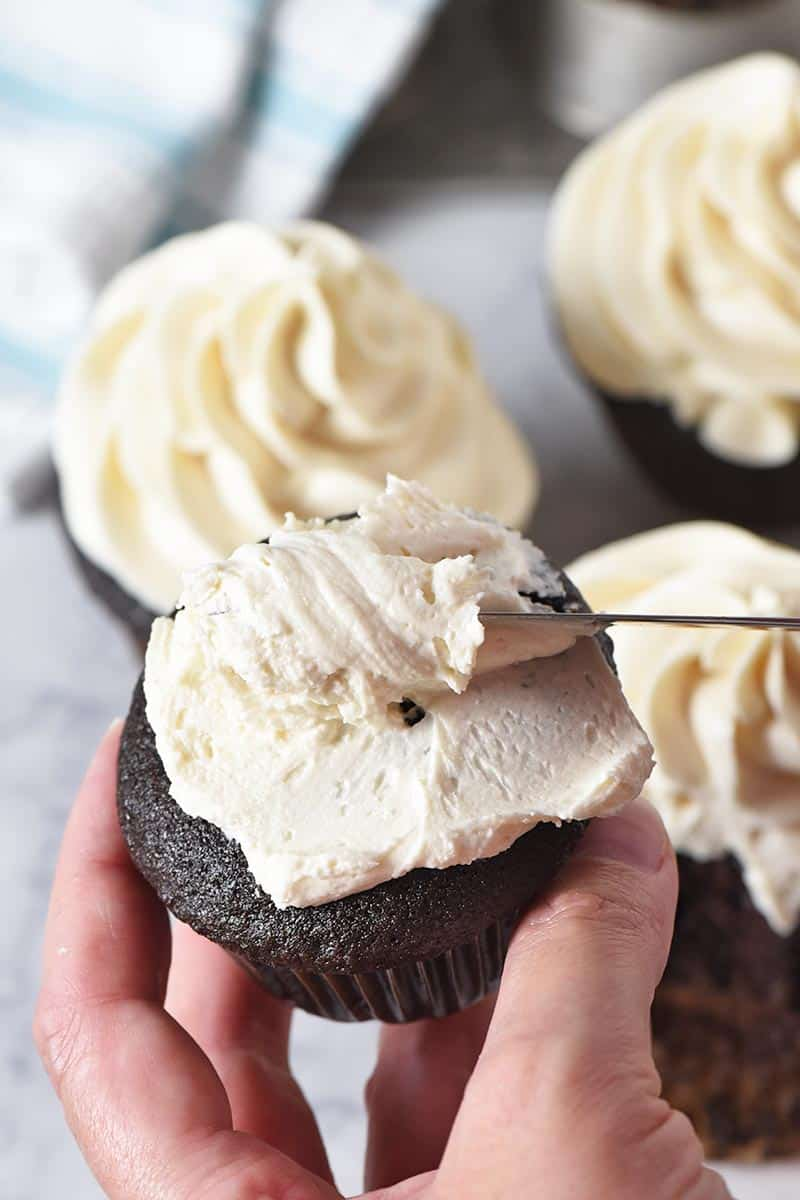 spreading butterbeer buttercream frosting onto dark chocolate cupcakes with a table knife