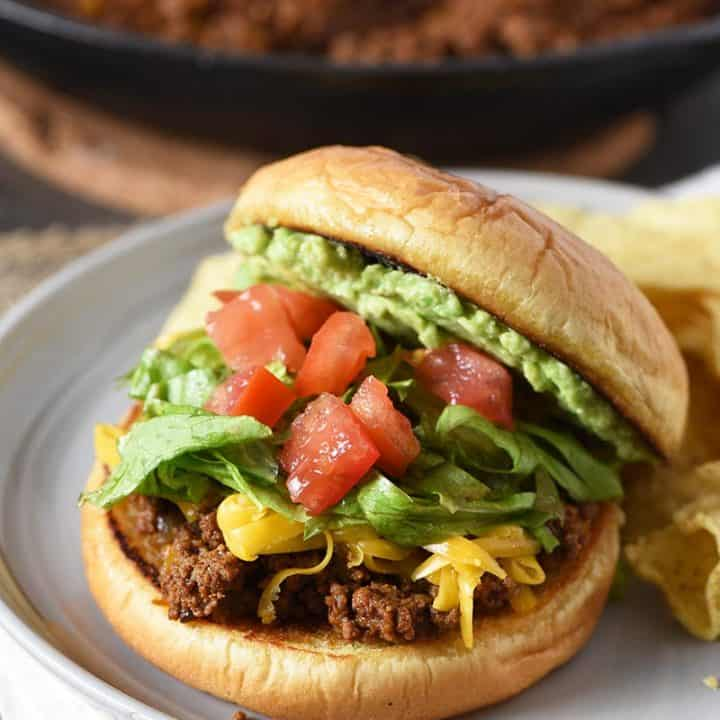 open faced taco sloppy joes sandwich with avocado, chopped tomatoes, lettuce, and shredded cheddar on a gray plate with tortilla chips