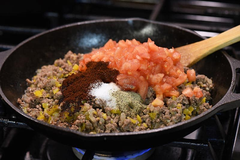 adding ingredients for taco seasoning to taco sloppy joes meat in cast iron skillet on stovetop