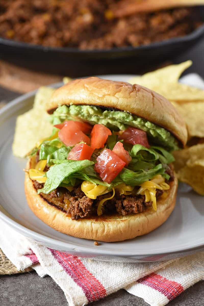 taco ingredients like avocado, tomatoes, lettuce, and shredded cheddar piled on sloppy joes on gray plate with tortilla chips