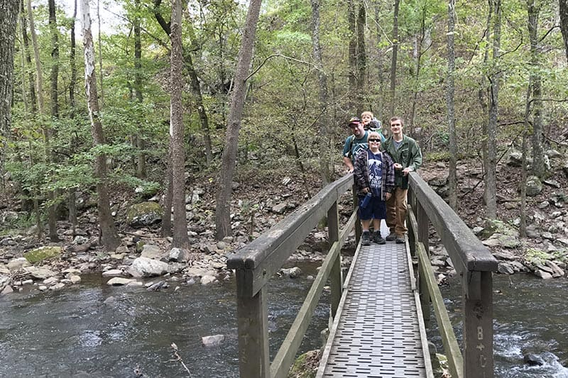family on footbridge crossing Cedar Creek in Petit Jean State Park, Arkansas