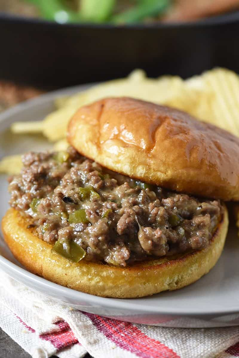 close up of Philly cheesesteak sloppy joes on gray plate with toasted hamburger bun and potato chips
