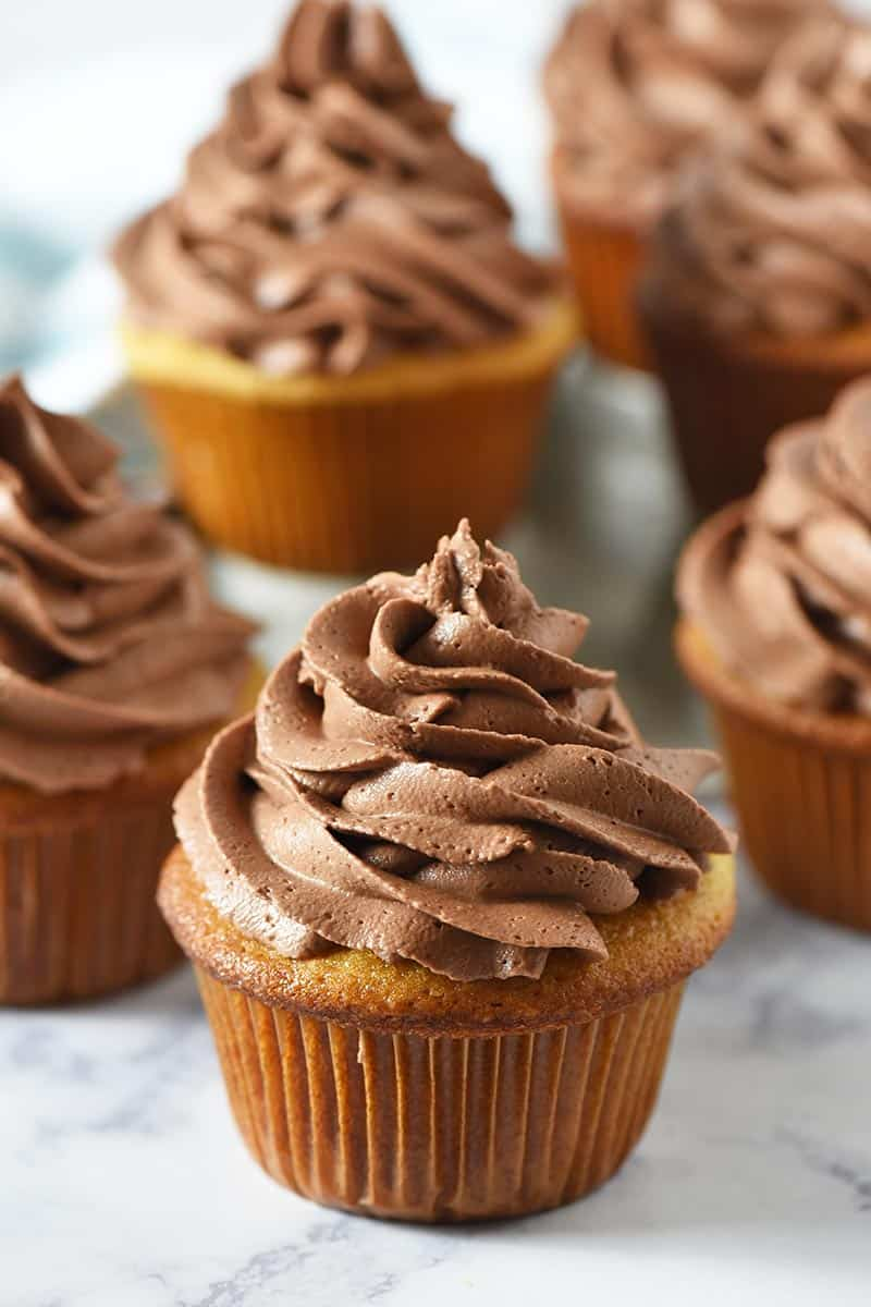 swirled chocolate frosting for piping on yellow cake cupcakes on white marble countertop