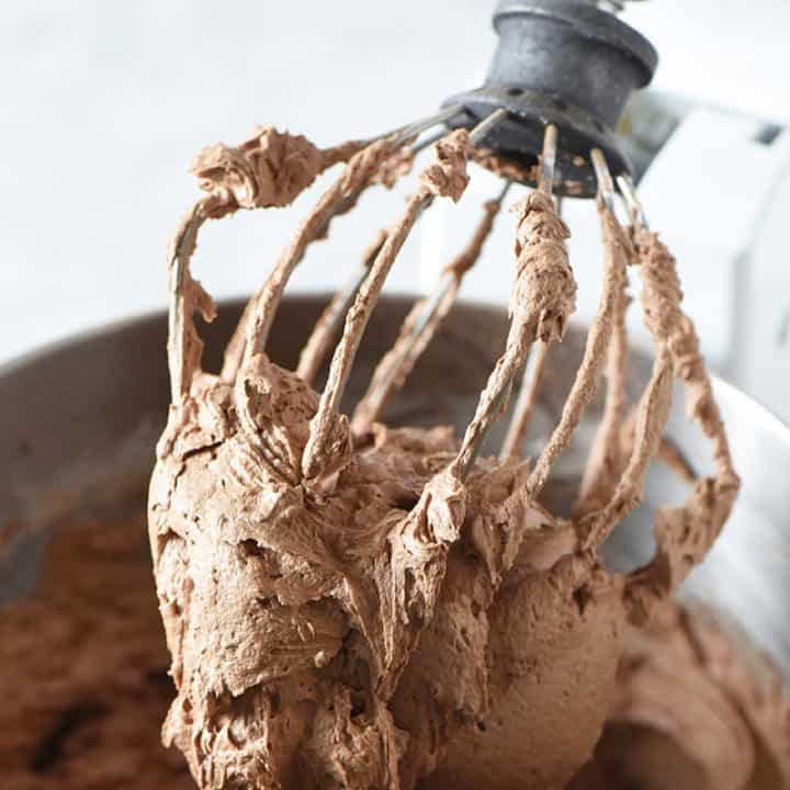mixing up chocolate buttercream frosting with KitchenAid mixing whisk