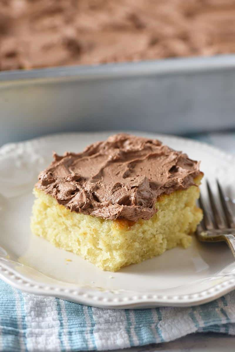 slice of yellow cake with chocolate buttercream frosting on an ivory plate with a fork