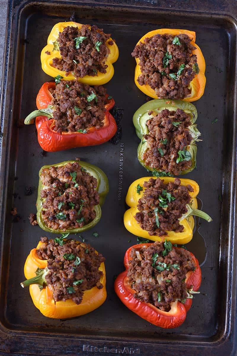 colorful sloppy joe stuffed bell peppers on a baking sheet