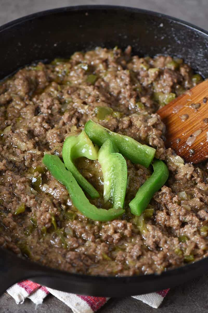 ground beef for Philly cheesesteak sloppy joes, cooked in cast iron skillet with green bell peppers and wooden spatula