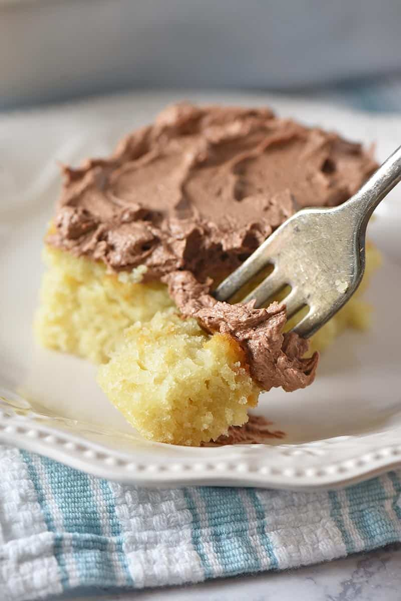 bite of yellow cake with chocolate frosting on a fork with ivory plate and blue and white striped kitchen towel