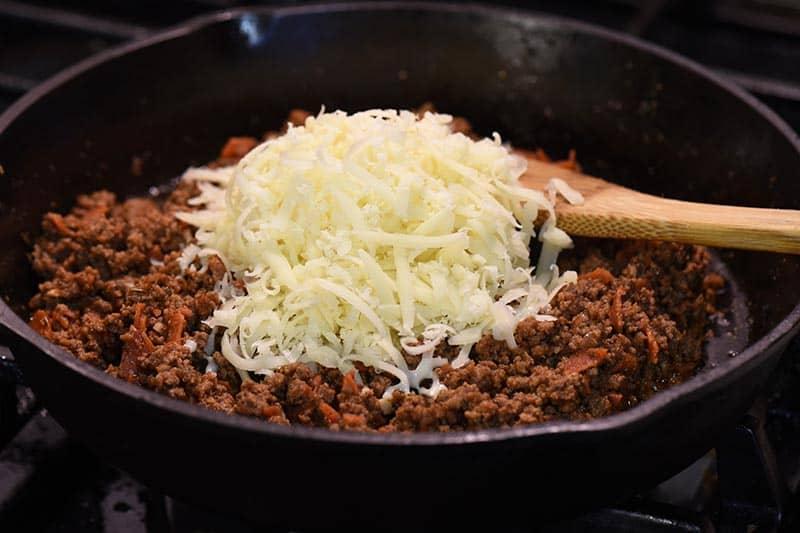 adding mozzarella cheese to pizza sloppy joes meat in iron skillet