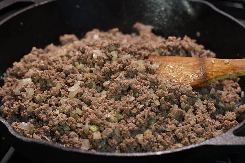 cooking ground beef, onion, and garlic for sloppy joe stuffed peppers recipe in cast iron skillet on stovetop