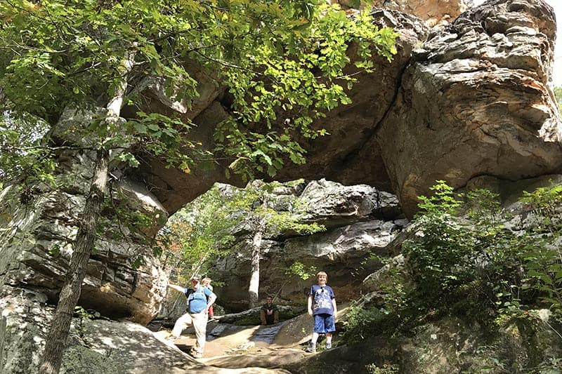 dad and sons posing with Natural Bridge on Arkansas hiking trail, Seven Hollows Trail, in Petit Jean State Park