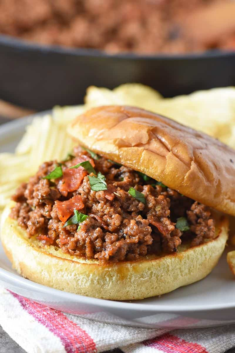 open faced pizza sloppy joes on toasted buns with potato chips, served on a gray plate