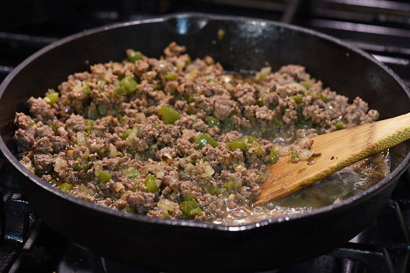 ground beef and veggie mixture for Philly cheesesteak sloppy joes, cooking in cast iron skillet