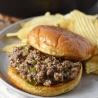 open faced Philly cheesesteak sloppy joes on toasted hamburger buns with potato chips on gray plate
