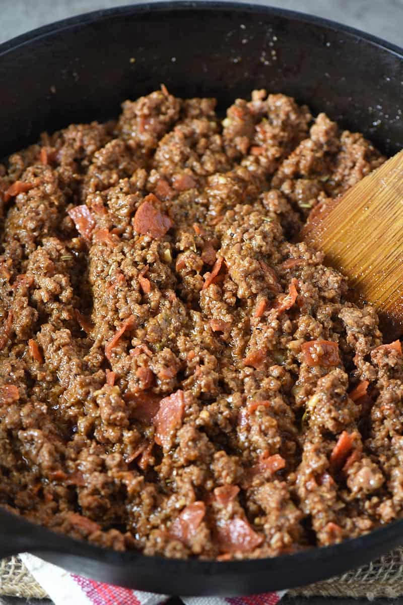 ground beef mixture for pizza joes, with wooden spatula in iron skillet