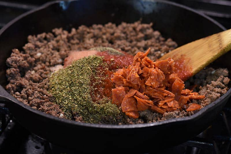 ingredients for pizza sloppy joe sauce in iron skillet with wooden spatula